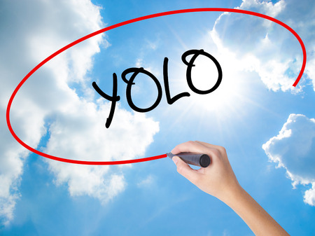 seize: Woman Hand Writing YOLO (You Only Live Once) with black marker on visual screen. Isolated on Sunny Sky. Business concept. Stock Photo Stock Photo