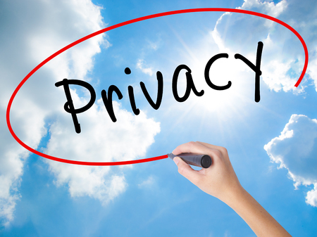 Woman Hand Writing Privacy with black marker on visual screen. Isolated on Sunny Sky. Business concept. Stock Photo