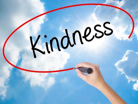 altruismo: Mujer ESCRITURA DE LA MANO La bondad con marcador negro en la pantalla visual. Aislado en Sunny Sky. Negocios, la tecnología, el concepto de internet.