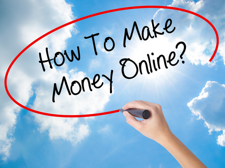 Woman Hand Writing How To Make Money Online? with black marker on visual screen. Isolated on Sunny Sky. Business concept. Stock Photo Stock Photo