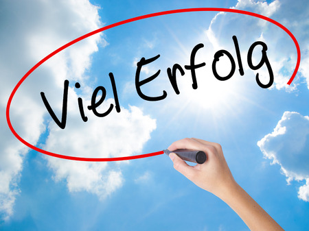 Woman Hand Writing Viel Erfolg (Much Success In German) with black marker on visual screen. Isolated on Sunny Sky. Business concept. Stock Photo
