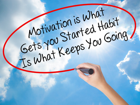 Woman Hand Writing Motivation is What Gets you Started Habit Is What Keeps You Going with black marker on visual screen. Isolated on Sunny Sky. Business concept. Stock Photo