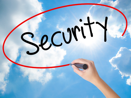 Woman Hand Writing Security with black marker on visual screen. Isolated on Sunny Sky. Business,  technology, internet concept. Stock Photo Stock Photo