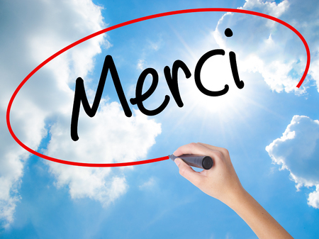 comunicación escrita: Woman Hand Writing Merci  (Thank You In French) with black marker on visual screen. Isolated on Sunny Sky. Business concept. Stock Photo Foto de archivo