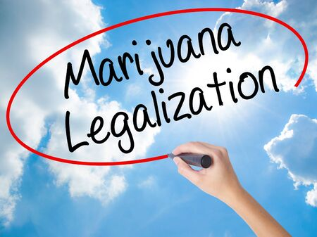 Woman Hand Writing Marijuana Legalization with black marker on visual screen. Isolated on Sunny Sky. Live, technology, internet concept. Stock Photo