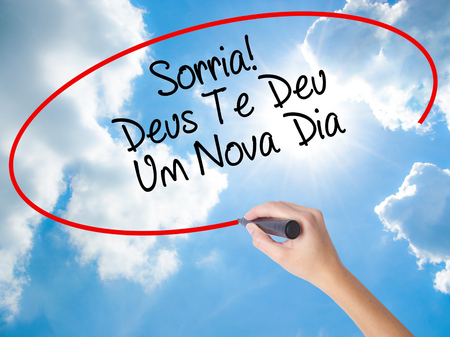 Woman Hand Writing Sorria! Deus Te Deu Um Novo Dia (Smile! God Gives You Another Day in Portuguese) with black marker on visual screen. Isolated on Sunny Sky. Business,  internet concept. Stock Photo