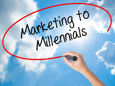demografia: Woman Hand Writing Marketing to Millennials with black marker on visual screen. Isolated on Sunny Sky. Business concept. Stock Photo Foto de archivo