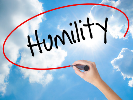 Woman Hand Writing Humility  with black marker on visual screen. Isolated on Sunny Sky. Business concept. Stock Photo