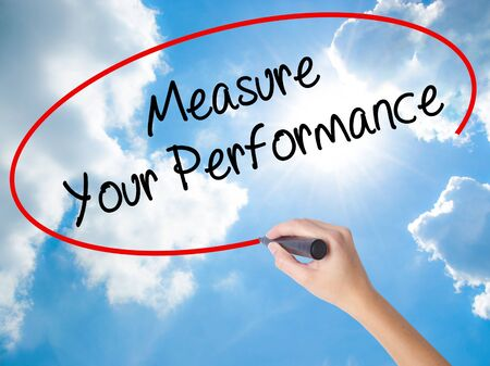 Woman Hand Writing Measure Your Performance with black marker on visual screen. Isolated on Sunny Sky. Business concept. Stock Photo Stock Photo