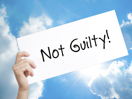 white backing: Man Hand Holding Paper with text NOT GUILTY . Sign on white paper. Isolated on Sky background.  Business concept. Stock Photo Stock Photo