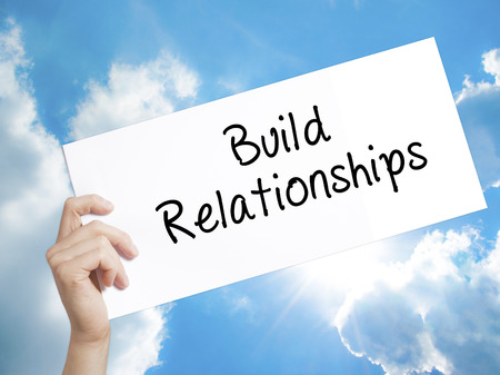 middleman: Man Hand Holding Paper with text Build Relationships . Sign on white paper. Isolated on Sky background.  Business concept. Stock Photo Stock Photo