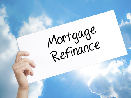 refinancing interest rates: Man Hand Holding Paper with text Mortgage Refinance . Sign on white paper. Isolated on Sky background.   Business concept. Stock Photo