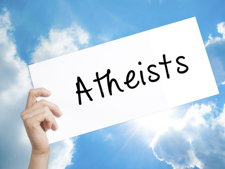 nonbelief: Man Hand Holding Paper with text Atheists . Sign on white paper. Isolated on Sky background.  Business concept. Stock Photo
