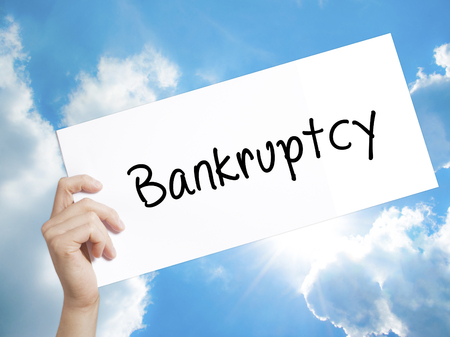 Man Hand Holding Paper with text Bankruptcy . Sign on white paper. Isolated on Sky background.  Business concept. Stock Photo Stock Photo