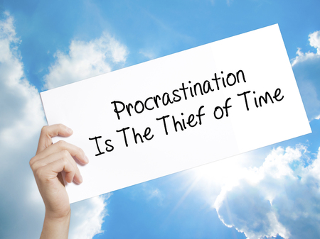 Man Hand Holding Paper with text  Procrastination Is The Thief of Time . Sign on white paper. Isolated on Sky background.  Business concept. Stock Photo