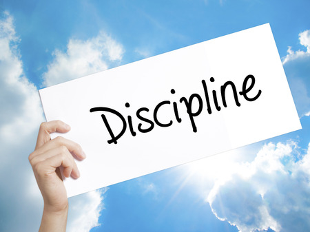 disciplined: Man Hand Holding Paper with text Discipline . Sign on white paper. Isolated on Sky background.   Business concept. Stock Photo
