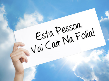 Man Hand Holding Paper with text Esta Pessoa Vai Cair Na Folia! (This Person Will be at Carnaval in Portuguese) . Sign on white paper. Isolated on Sky background.  Business concept. Stock Photo