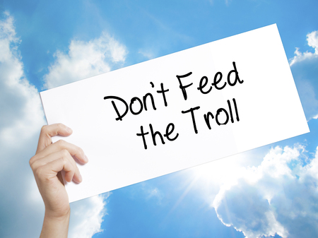 Man Hand Holding Paper with text Dont Feed the Troll . Sign on white paper. Isolated on Sky background.  Business concept. Stock Photo