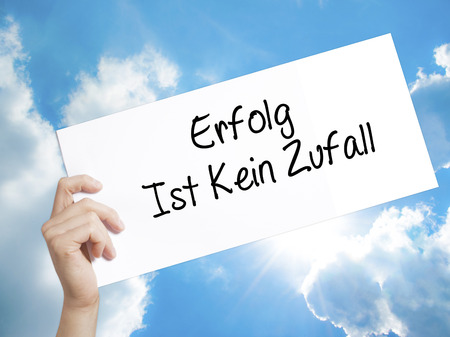 Man Hand Holding Paper with text Erfolg Ist Kein Zaufall (Success Is No Accident in German) . Sign on white paper. Isolated on Sky background.  Business concept. Stock Photo