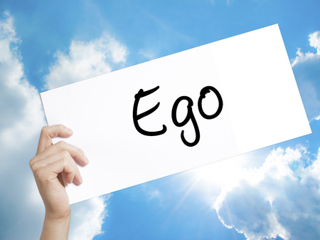 Man Hand Holding Paper with text Ego . Sign on white paper. Isolated on Sky background.  Business concept. Stock Photo