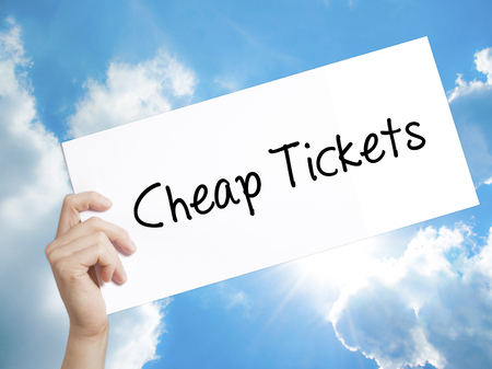 miles: Man Hand Holding Paper with text Cheap Tickets . Sign on white paper. Isolated on Sky background.  Business concept. Stock Photo