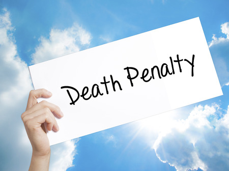 Man Hand Holding Paper with text Death Penalty . Sign on white paper. Isolated on Sky background.  Business concept. Stock Photo