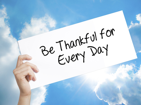 humility: Man Hand Holding Paper with text Be Thankful for Every Day   . Sign on white paper. Isolated on Sky background.   Business concept. Stock Photo