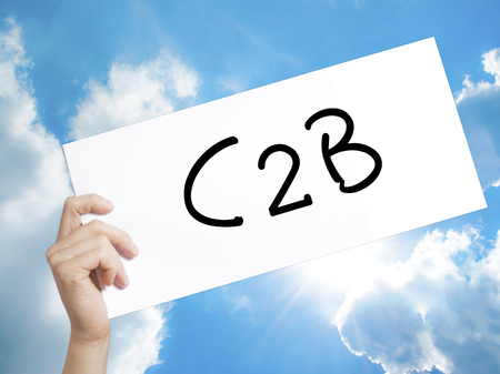 sourcing: Man Hand Holding Paper with text C2B . Sign on white paper. Isolated on Sky background.  Business concept. Stock Photo