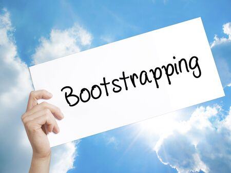 bootstrap: Man Hand Holding Paper with text Bootstrapping . Sign on white paper. Isolated on Sky background.  Business concept. Stock Photo Stock Photo