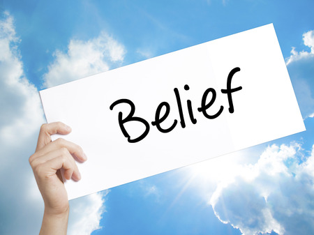 Man Hand Holding Paper with text Belief . Sign on white paper. Isolated on Sky background.   Business concept. Stock Photo