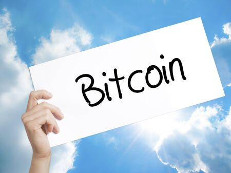 net trade: Man Hand Holding Paper with text Bitcoin . Sign on white paper. Isolated on Sky background.  Business concept. Stock Photo