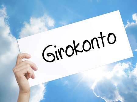 girokonto: Man Hand Holding Paper with text  Girokonto (Checking Account) . Sign on white paper. Isolated on Sky background.  Business concept. Stock Photo