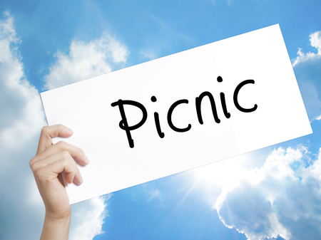 picknick: Man Hand Holding Paper with text Picnic . Sign on white paper. Isolated on Sky background.   Business concept. Stock Photo