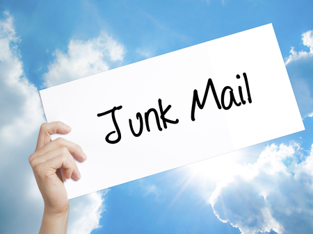 solicitors: Man Hand Holding Paper with text Junk Mail . Sign on white paper. Isolated on Sky background.   Business concept. Stock Photo