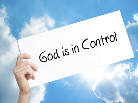 sanctification: Man Hand Holding Paper with text God is in Control . Sign on white paper. Isolated on Sky background.   Business concept. Stock Photo Stock Photo