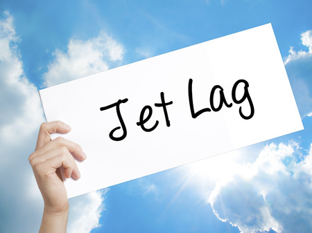 lag: Man Hand Holding Paper with text  Jet Lag . Sign on white paper. Isolated on Sky background.  Business concept. Stock Photo Stock Photo