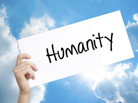 clemency: Man Hand Holding Paper with text Humanity  . Sign on white paper. Isolated on Sky background.  Business concept. Stock Photo Stock Photo