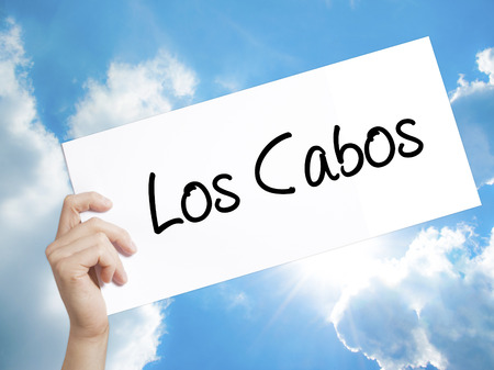 lucas: Man Hand Holding Paper with text Los Cabos . Sign on white paper. Isolated on Sky background.   Business concept. Stock Photo