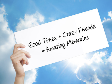 positiveness: Man Hand Holding Paper with text Good Times + Crazy Friends = Amazing Memories . Sign on white paper. Isolated on Sky background.  Business concept. Stock Photo Stock Photo