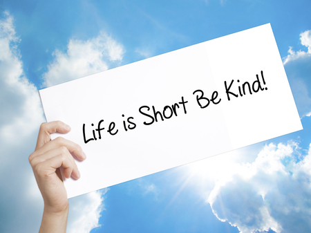 Man Hand Holding Paper with text Life is Short Be Kind! . Sign on white paper. Isolated on Sky background.   Business concept. Stock Photo