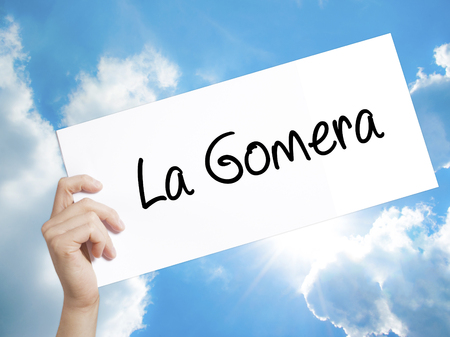sun s: Man Hand Holding Paper with text La Gomera . Sign on white paper. Isolated on Sky background.  Business concept. Stock Photo Stock Photo