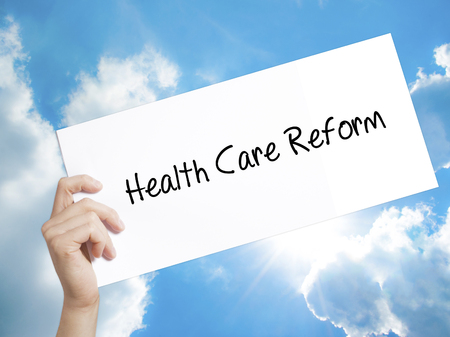 Man Hand Holding Paper with text Health Care Reform . Sign on white paper. Isolated on Sky background.  technology, internet concept.