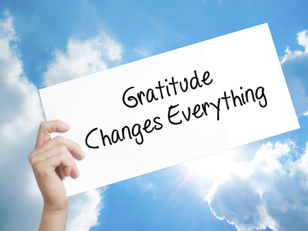 humility: Man Hand Holding Paper with text Gratitude Changes Everything . Sign on white paper. Isolated on Sky background.   Business concept. Stock Photo Stock Photo