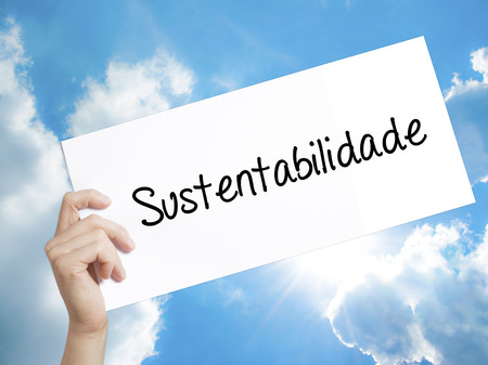 Man Hand Holding Paper with text Sustentabilidade (In portuguese - Sustainability) . Sign on white paper. Isolated on Sky background.  Business concept. Stock Photo