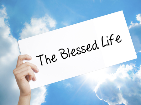 humility: Man Hand Holding Paper with text The Blessed Life  . Sign on white paper. Isolated on Sky background.  Business concept. Stock Photo