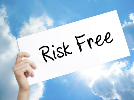 Man Hand Holding Paper with text Risk Free . Sign on white paper. Isolated on Sky background.  Business concept. Stock Photo