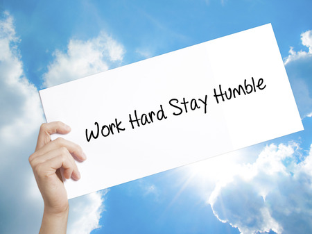 humility: Man Hand Holding Paper with text Work Hard Stay Humble  . Sign on white paper. Isolated on Sky background.  technology, internet concept.
