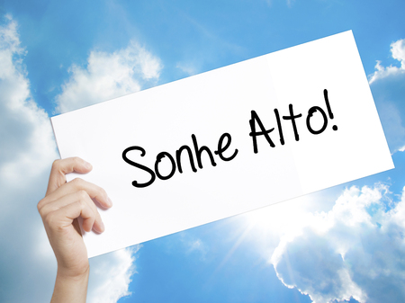 Man Hand Holding Paper with text Sonhe Alto! (Dream Big in Portuguese) . Sign on white paper. Isolated on Sky background. Business concept. Stock Photo Imagens