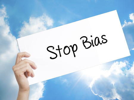 biased: Man Hand Holding Paper with text Stop Bias . Sign on white paper. Isolated on Sky background.  technology, internet concept.