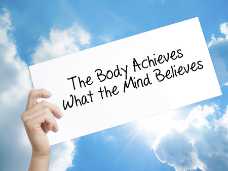 believes: Man Hand Holding Paper with text The Body Achieves What the Mind Believes . Sign on white paper. Isolated on Sky background.   Business concept. Stock Photo Stock Photo